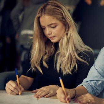 Koncentrerad elev skriver med penna.