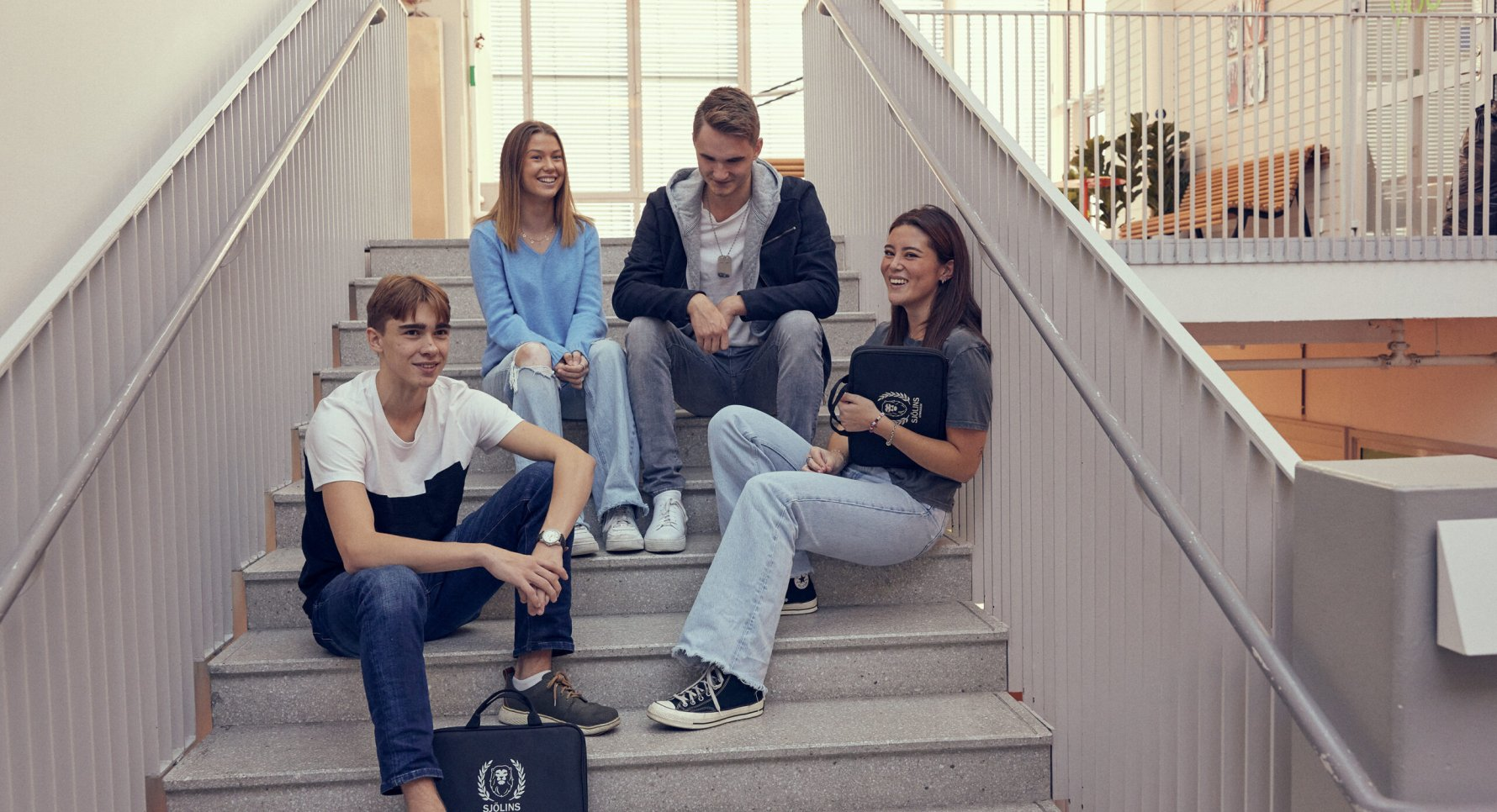 Elever sitter i trappa och hänger i Sjölins Gymnasium.