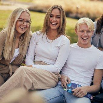 Tre glada elever utanför skolan.