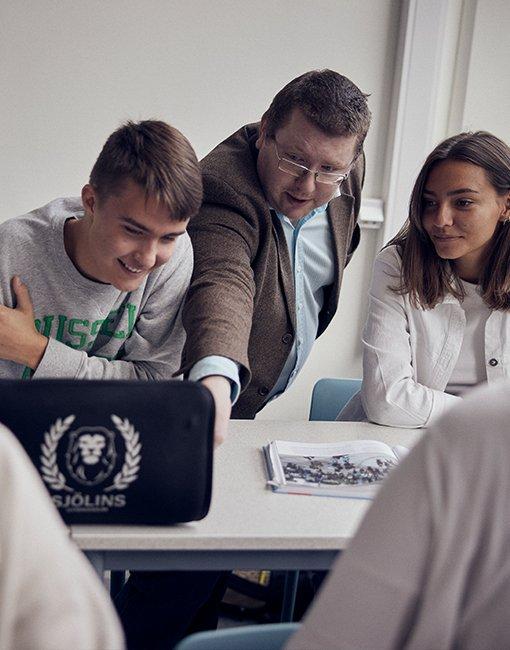 Lärare visar något på datorn för två elever på Sjölins Gymnasium.