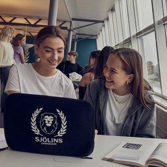 Två glada elever kollar på en skoldator.