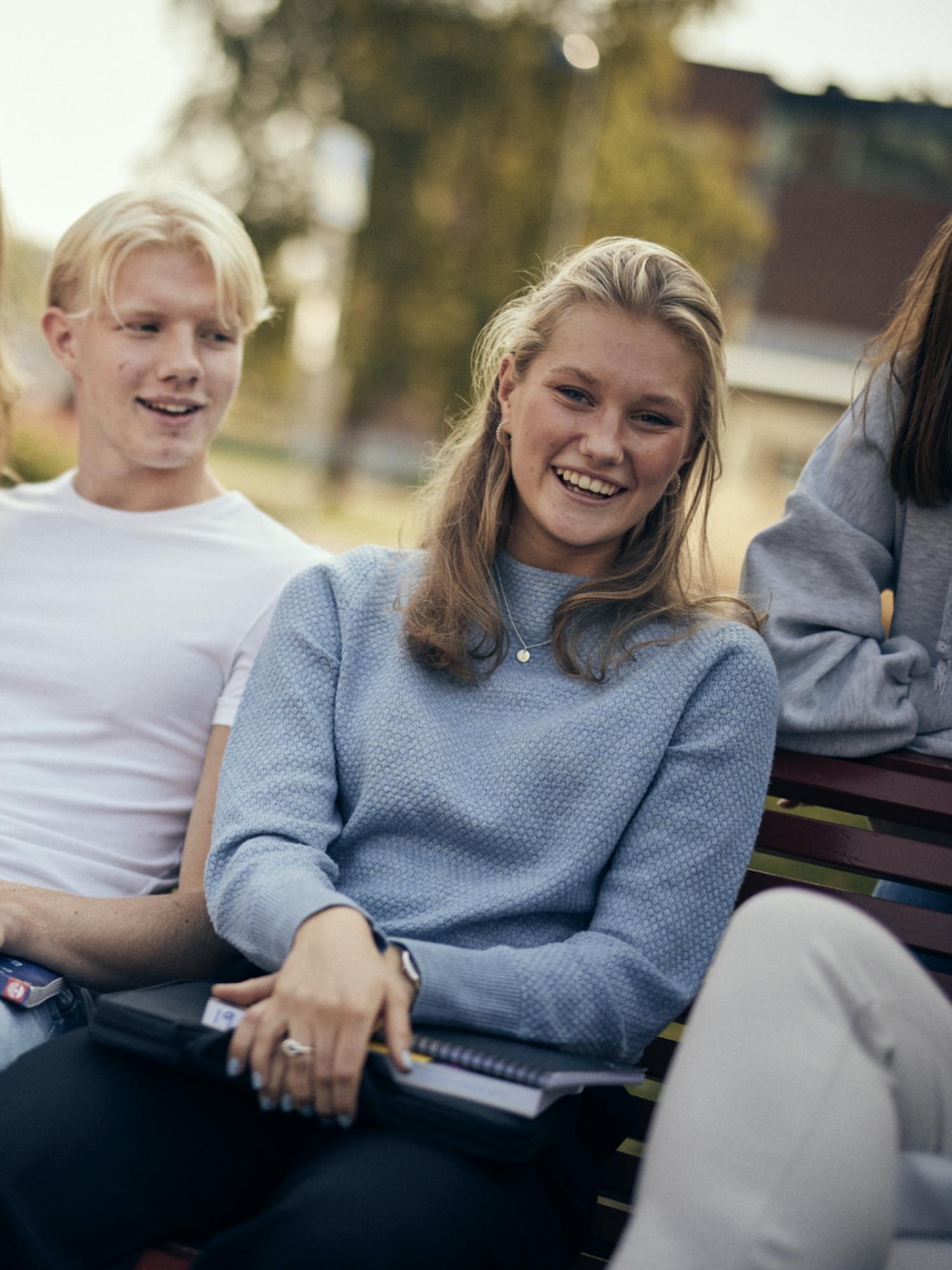 Elever sitter på en bänk utanför Sjölins Gymnasium.