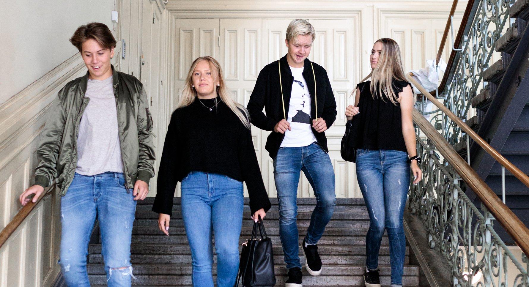 Elever går ned för trappan på Sjölins Gymnasium.