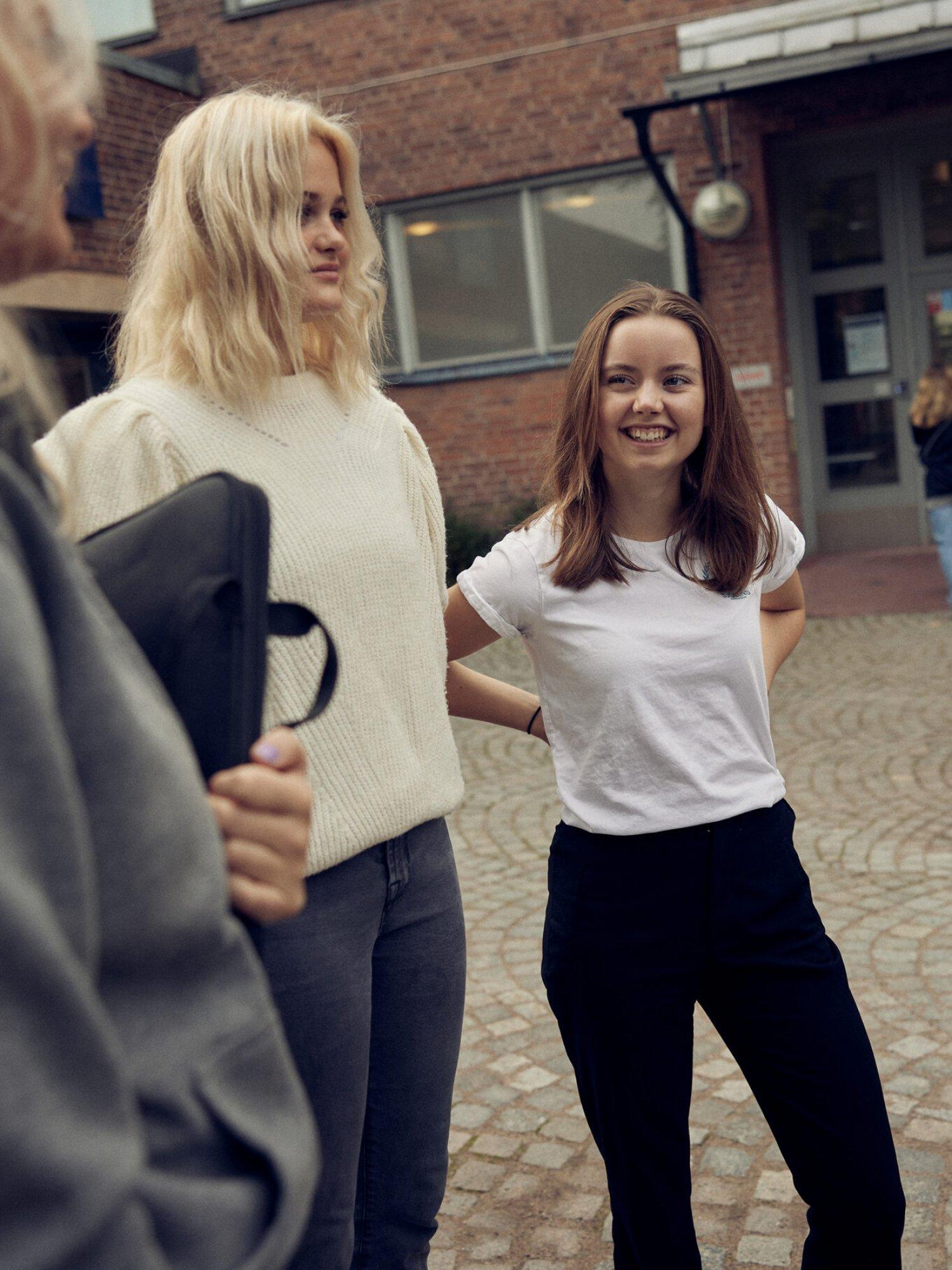 Elever står och pratar utanför ingången till Sjölins Gymnasium.