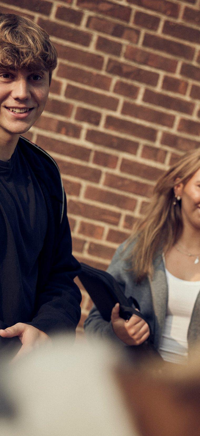 Två elever framför tegelvägg vid Sjölins Gymnasium.