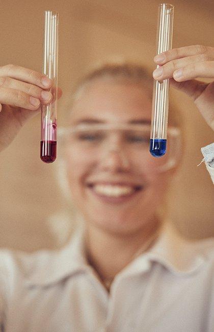 Två provrör hålls upp av elev i kemisalen på Sjölins gymnasium.