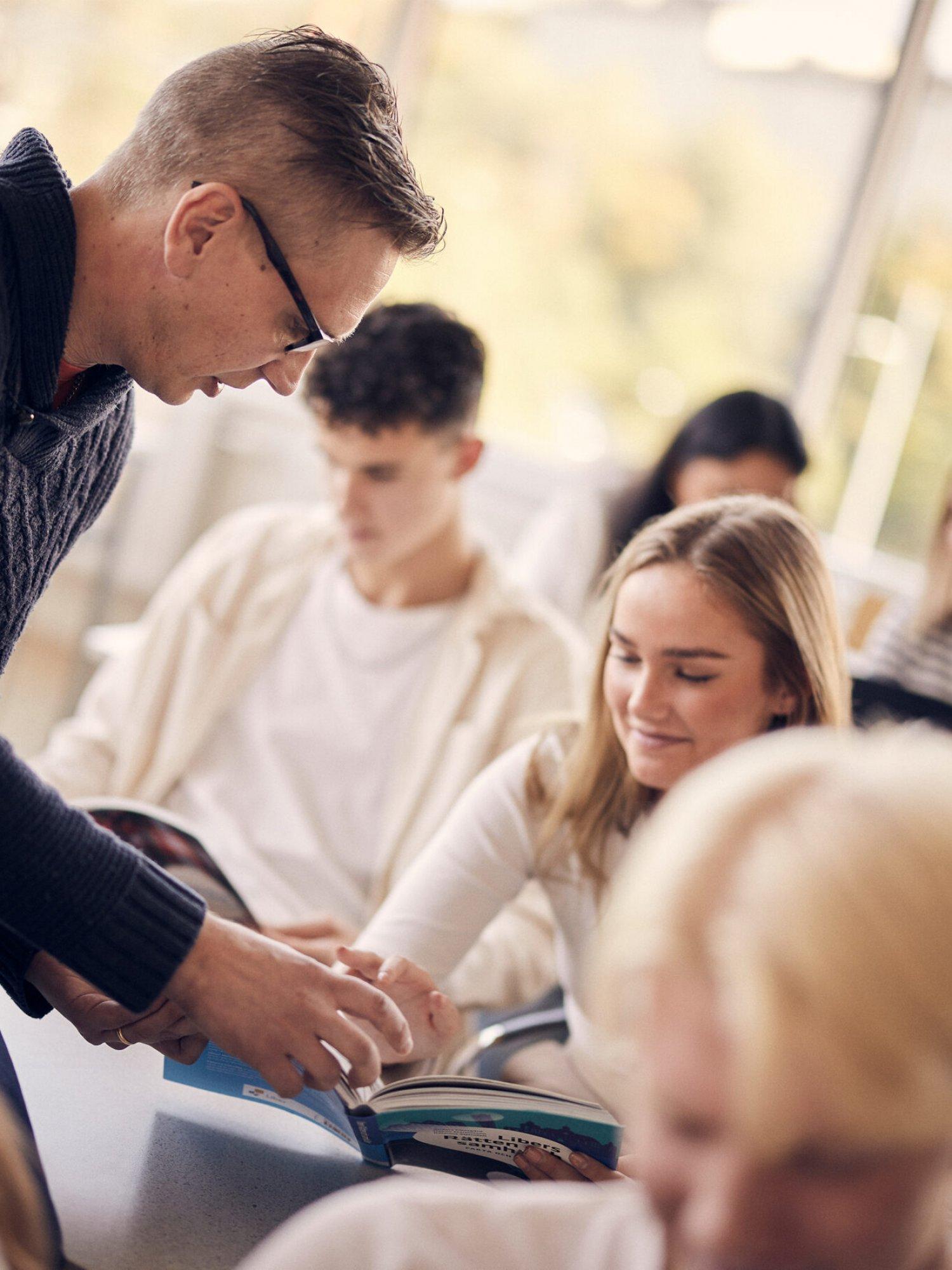 Lärare hjälper elev i klassrummet på Sjölins Gymnasium.