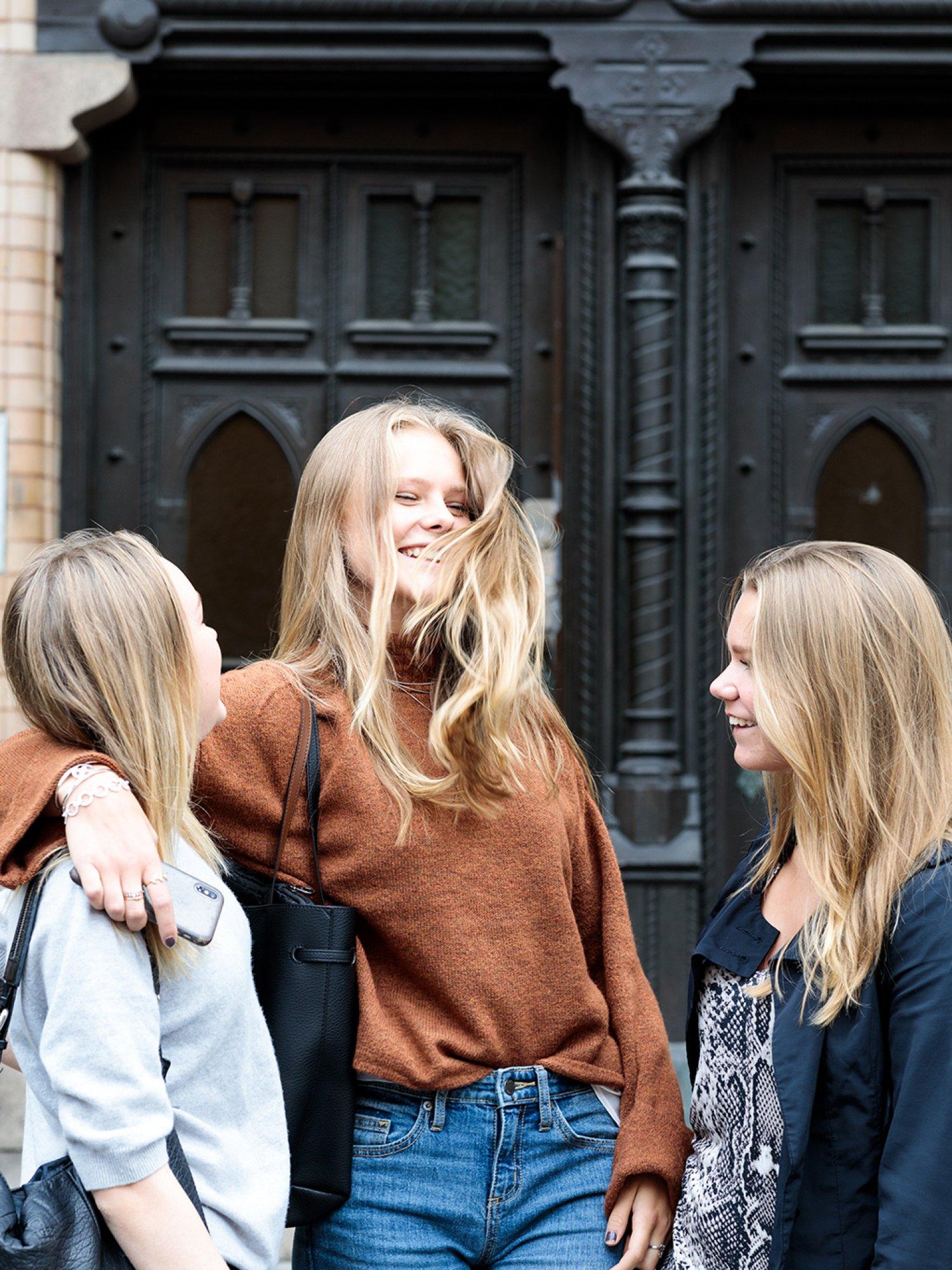 Tre tjejer hänger utanför Sjölins Gymnasium.